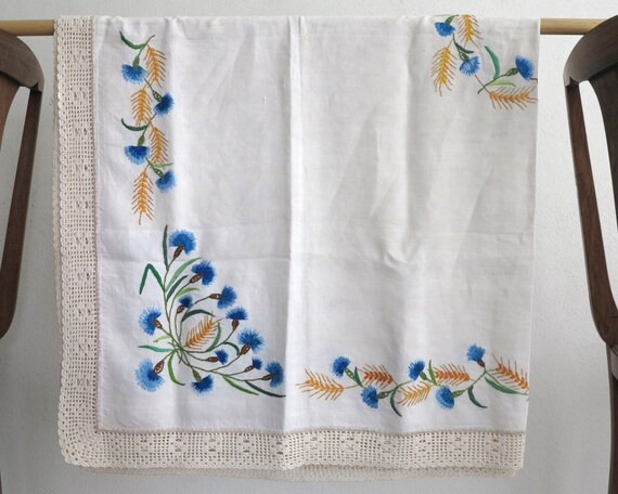 Mid 20th century hand embroidered tablecloth with Australian wildflowers in blue, gold, orange, wide hand crocheted edge, 53 ins x 50 ins