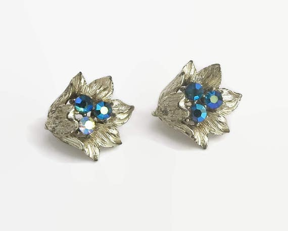 Flower earrings with blue Aurora Borealis rhinestones in the centers, pale gold tone metal setting, clip ons, circa 1950s