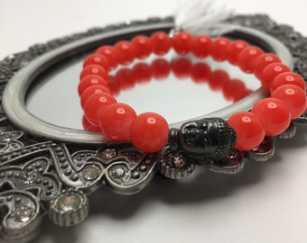 Bright/Neon Orange beaded flexible bracelet with a Pewter Buddha Head and White Tassel.