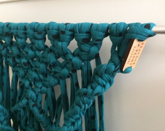 Macrame wallhanging in teal with black polkadots on an iron stick