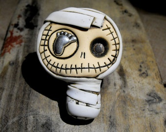 Happy baby mummy brooch in dirty white. Creepy and cute skull with a foot in his eye.