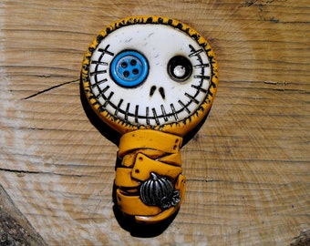 Smiling baby mummy bandaged in orange. He has a tiny pumpkin his body and a blue button in his eye. Brooch or magnet