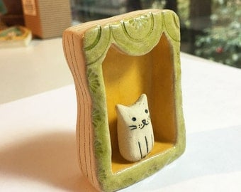 Pretty White Cat Sitting in a Little Curtained Stage Ceramic Wall Sculpture