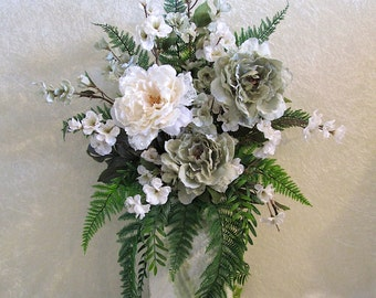 large silk flower arrangement in a green and white swirl patterned ceramic vase with light green