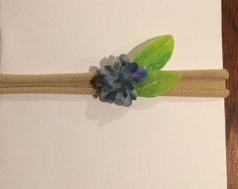 Small bluish purple flower with leaves on nylon