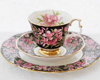 """Royal Albert's  """"Fire Weed"""" a black chintz trio teaset; pale pink flowers and green-yellow leaves, c1970-1980s"""