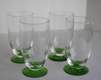 4 Clear glass tumblers with green pedestal base