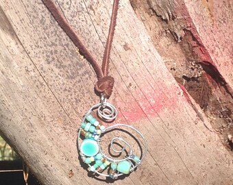 Beaded and silver wire pendant on brown leather cord with turquoise beads