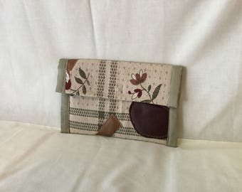 Envelope purse tapestry and leather . Purse is lined with Hawaiian fabric .