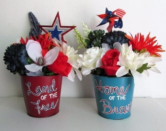 "Set of 2 Hand-Painted Patriotic themed Silk Flower Arrangement Pails, featuring ""Land of the Free"" and ""Home of the Brave,"" & Picks"