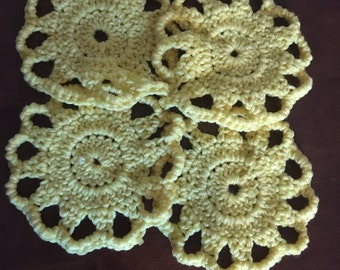 Handmade yellow crochet beverage coasters