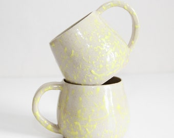 two yellow dripping cups, mugs, shiny, dripping, ceramic, glazed