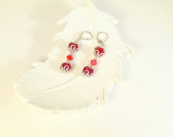 Red bead with silver filigree, red Swarovski crystals and silver lever back ear wires.