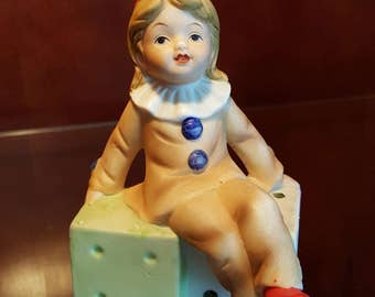 Royal Crown Porcelain Figurine Depicting A Child Dressed In Clown Attire While Sitting On A Pair Of Dice, Made In Taiwan c1960's/70's