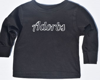 Adorable toddler infant shirt long sleeve with the word adorbs written on it.  Raised lettering with glitter sparkles, black tee