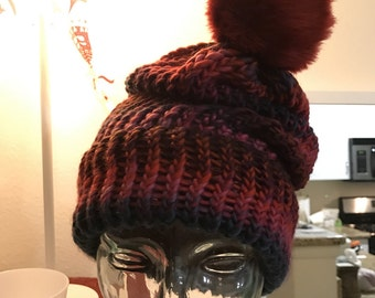 Multi-color red slouchy beanie. Topped with red faux fur pom-pom. Hand made.