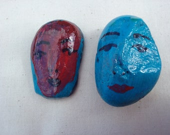 Two small, painted faces, drawn in pen and ink. Cute and evocative faces. Painted stone faces.