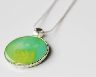 Aqua and a splash of gold, in this resin pendant, for your beachy look.