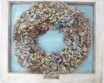 Vintage window with dried hydrangea wreath on painted burlap