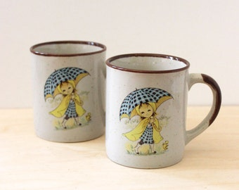 Rainy Day. Pair of 1970s stoneware coffee mugs featuring little girls in raincoats.
