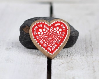 wooden heart brooch with hand drawn red design on white