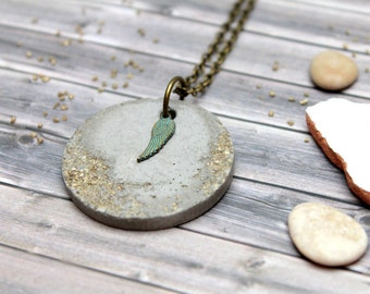 Concrete necklace with metal wing and golden stones