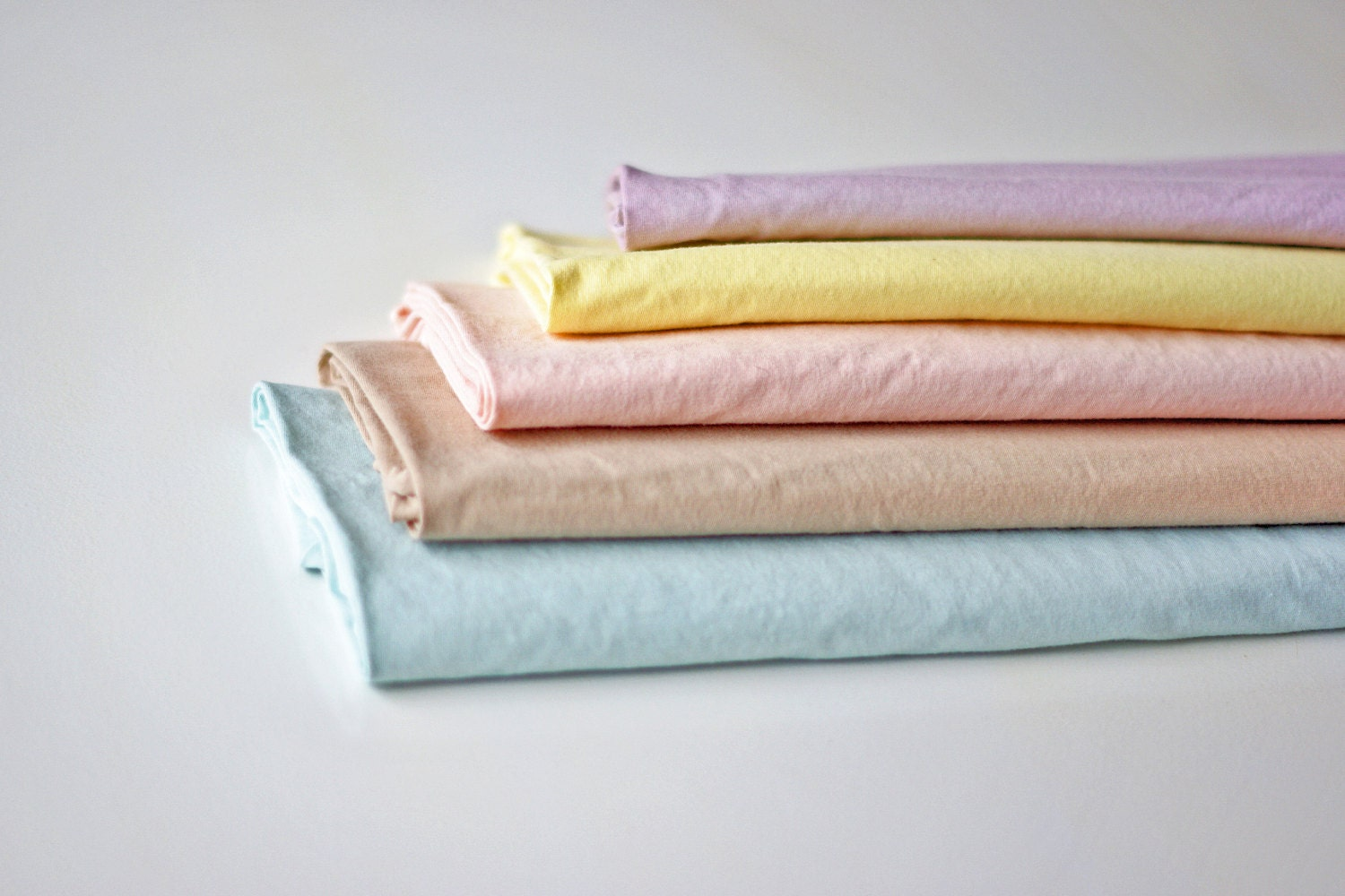 Natural dyes in pastel shades of aqua, beige, pink, yellow and purple.