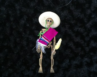 Pink Sarape day of the dead skeleton ornament with an elote (corn)