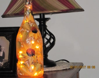 Frosted Wine bottle with sunflowers green leaves white baby breath hand painted throughout the bottel lights inside