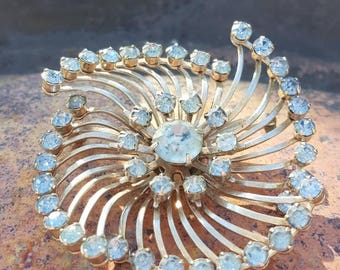 Unique fan style brooch. Light blue rhinestones