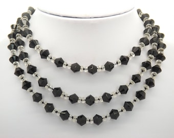 A beautiful period very long crystal bead vintage jewelry necklace made up of sparkly faceted black and clear crystal spacer beads