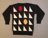 1980's, long, slit-neck, sweater, with white triangles, and red and yellow octagons, Women's size Medium/Large