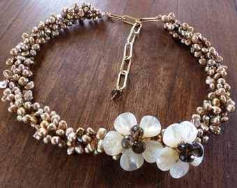 Daisy Chain Choker is braided strands of bronze keishi pearls blooming with a pair of mother-of-pearl flowers with smoky quartz centers.