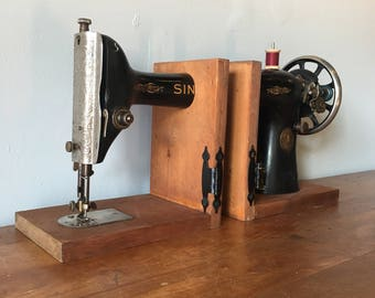 Vintage singer sewing machine bookends on salvaged wood