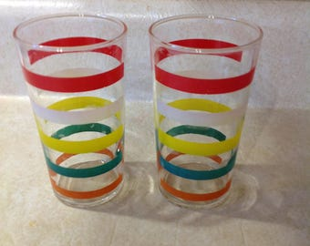 Two (2) clean anchor hocking juice glasses! Clear glass red, white, yellow, green and orange stripes!