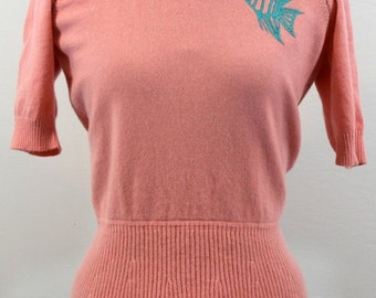 Coral cashmere sweater w/ scoop neckline and gathered waist w/ small skirt. Embroidered with an angel fish design. Originally b