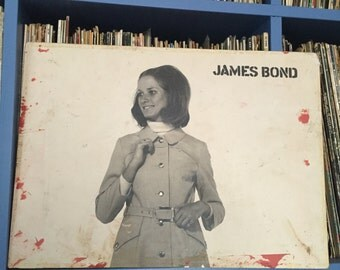 1960s French Shop Sign marked 'James Bond'. Shop Display. Vintage Fashion Advertising. Black and White Woman Raincoat. Midcentury Wall Decor