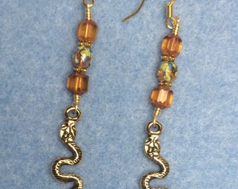 Gold snake charm earrings adorned with yellow orange Czech glass beads.