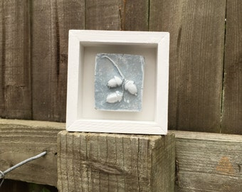 Framed original wall art, rustic clay impression of three acorns, pale blue and white in a white wooden box frame.