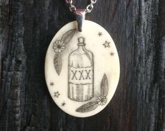 Rum Bottle/Poison Bottle: scrimshaw pendant on bone
