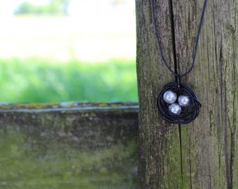 black/silver birds nest necklace with 3 eggs