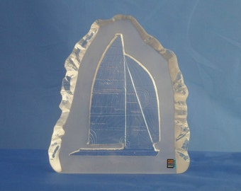 A crystal glass block paperweight by Pukeberg Glasbruk of Sweden. Rare paperweight featuring racing yacht in full sail.