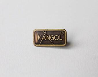 Vintage Kangol pin. Mangold brooch. Kangol badge. Kangol brown and gold tone brand lapel pin, promotional badge.