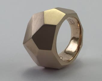 faceted ring of medium size, strong structural nature, perfect planes, reminiscent of a crystal, bronze.