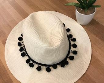 White Panama hat with black pompoms
