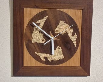 Three fish clock, hardwood veneer inlay in solid walnut frame.