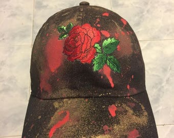 Black red rose with red and gold paint splatter