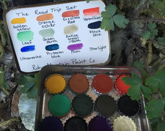 The Road Trip Set.  A handmade watercolor paint set featuring 12 bottle caps of handmade watercolors in a vintage cigar tin.