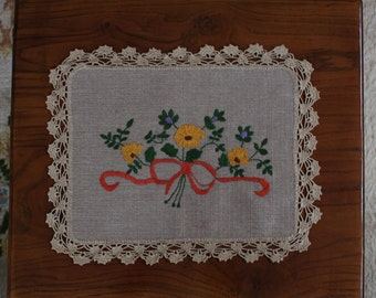 Handmade embroidered tablecloth with lace edges.