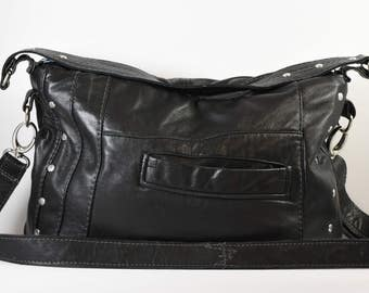Upcycled, repurposed leather, shoulder handbag with removeable cross-body strap, zippered closure, and decorative rivets.